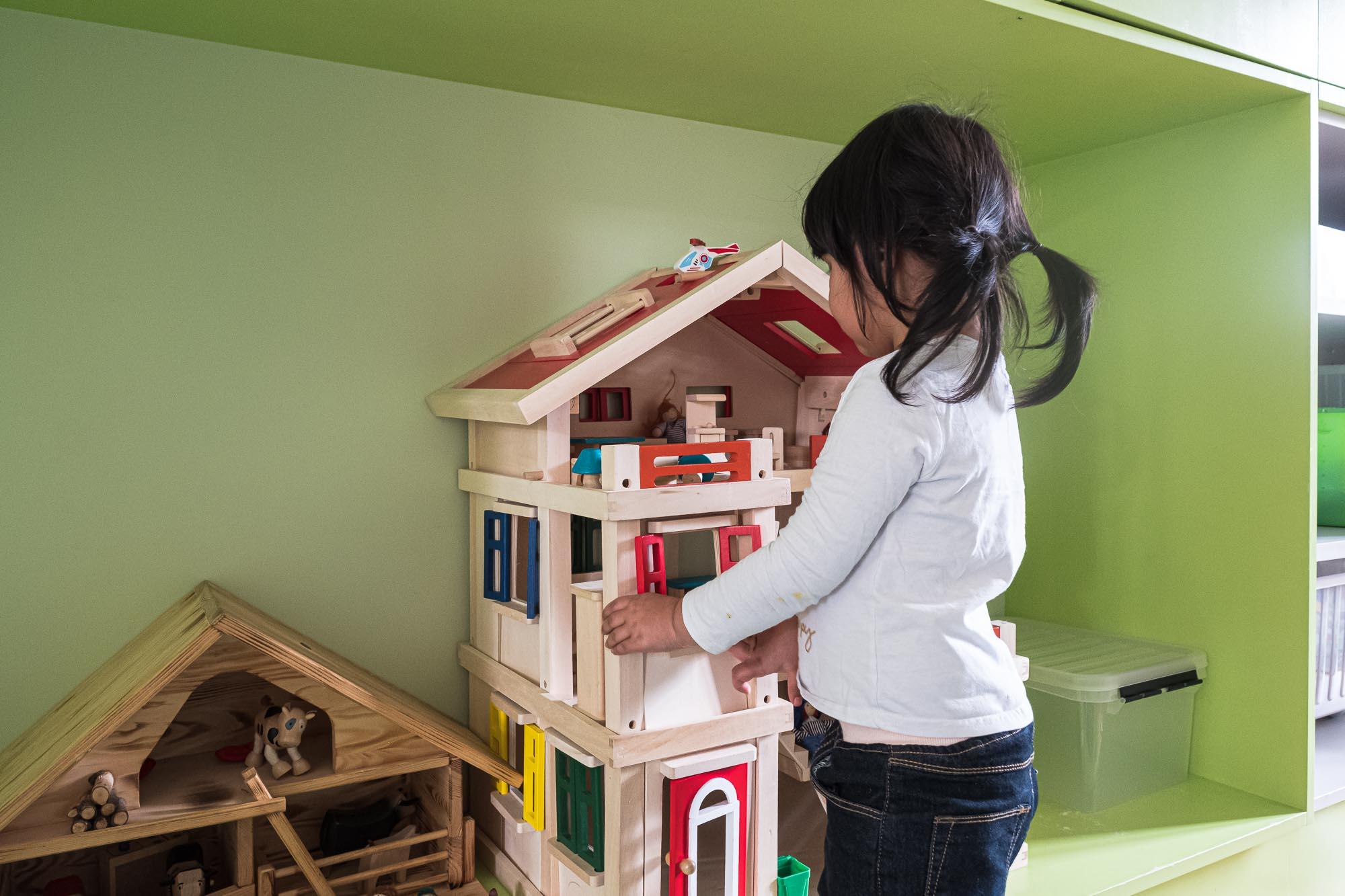 Kind vor Puppenhaus