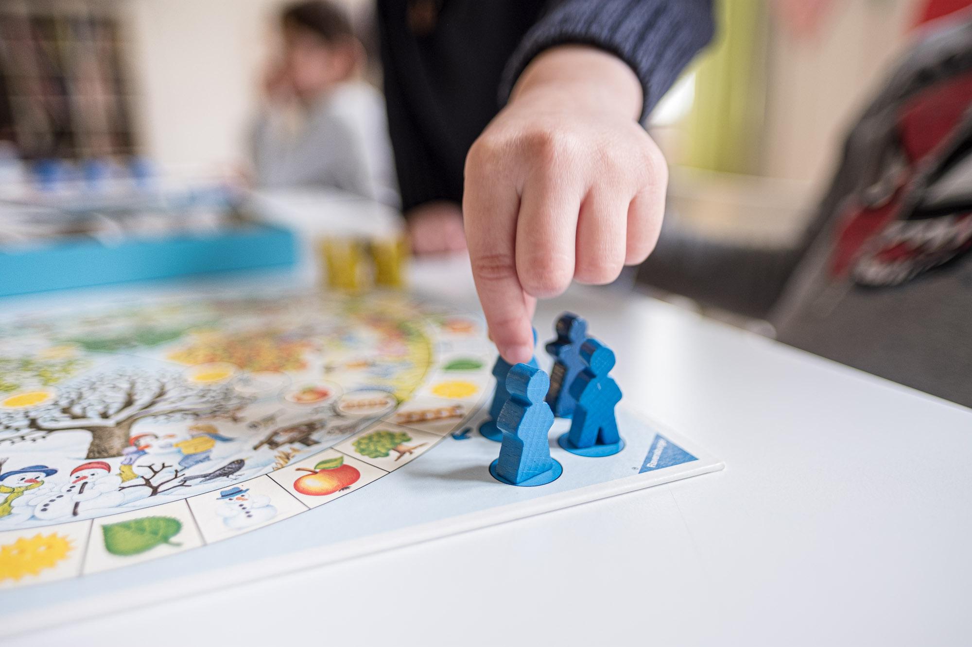 Kinderhand an Spielfigur